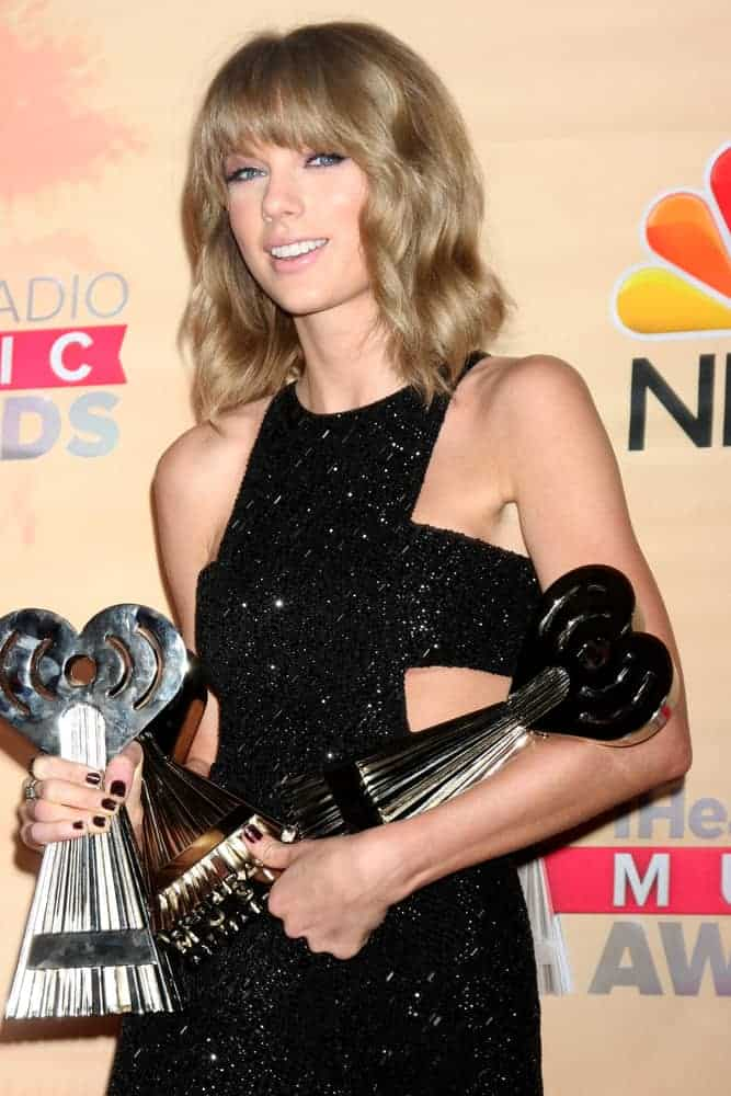 Taylor Swift sported a medium-length hairstyle with full bangs at the 2015 iHeartRadio Music Awards. This trendy look fits perfectly in her daring short dress.