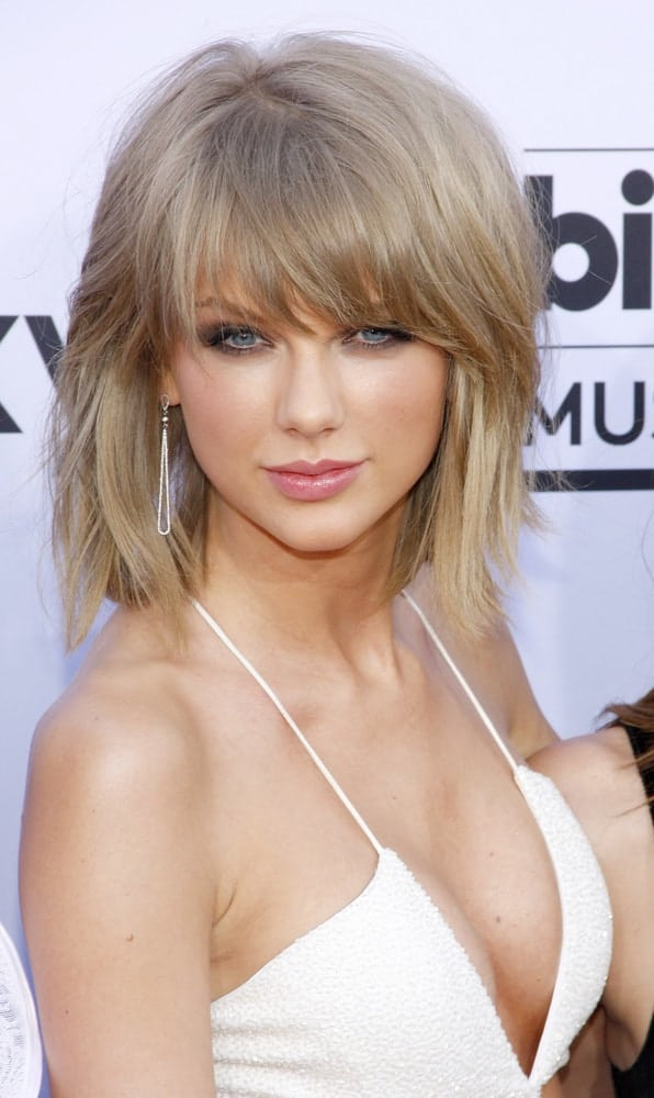 Taylor Swift looked seductive in a white jumpsuit along with a frizzy mid-length bob incorporated with fringe. This was taken at the 2015 Billboard Music Awards.