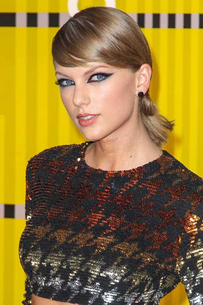 Taylor Swift looking all cool and trendy in her mid-rib outfit at the 2015 MTV Video Music Awards. She complemented it with a low ponytail bun and side-swept bangs.