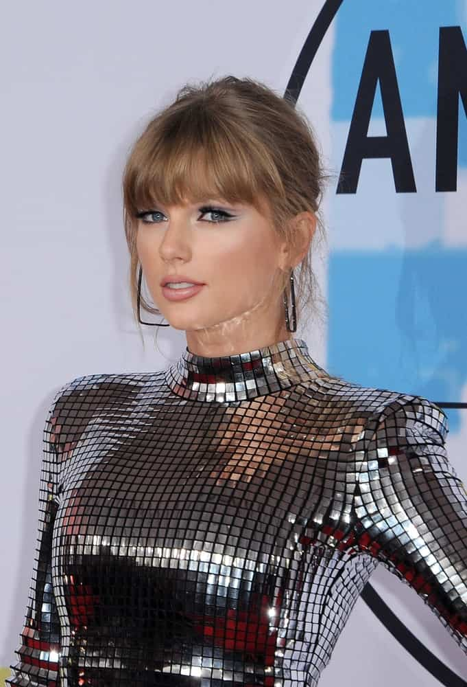 Taylor Swift shines in a silver turtleneck dress paired with a messy upstyle and bangs at the 2018 American Music Awards held at the Microsoft Theater on October 9th.