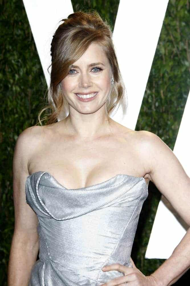Amy Adams attended the Vanity Fair Oscar Party at Sunset Tower on February 26, 2012, in West Hollywood, California. She was stunning in a silver strapless dress that she topped with a messy bun hairstyle with loose long side-swept bangs.