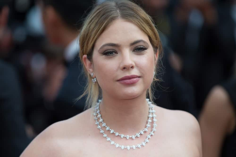 Ashley Benson attended the 70th Anniversary screening premiere at the 70th Festival de Cannes on May 23, 2017. She paired her strapless dress with an elegant necklace and a messy bun hairstyle with loose tendrils and long side bangs.