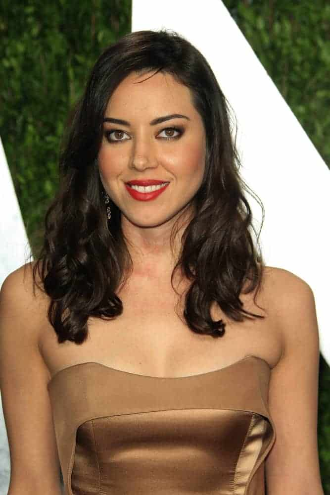 Aubrey Plaza attended the Vanity Fair Oscar Party at Sunset Tower on February 24, 2013, in West Hollywood, California. Her strapless dress was paired with a long loose and tousled dark hairstyle that has curls at the tips.