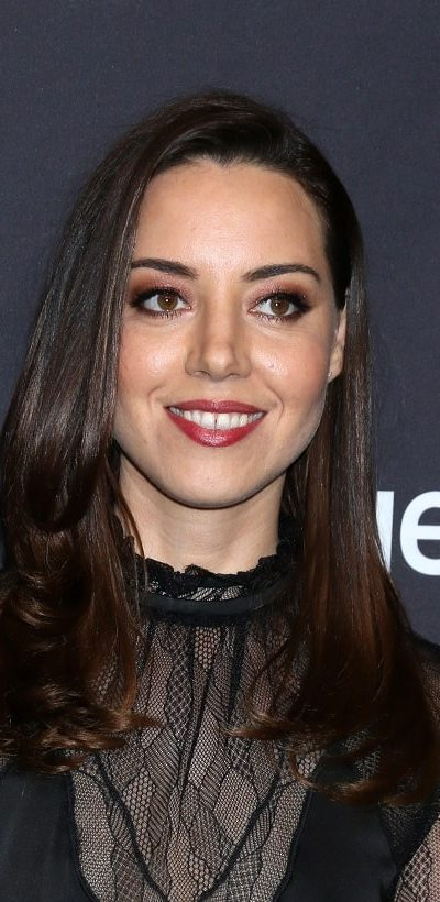"""Aubrey Plaza was at the PaleyFest - """"Parks and Recreation"""" 10th Anniversary Reunion at the Dolby Theater on March 21, 2019 in Los Angeles, CA. She was sexy and stunning in a black sheer dress that she paired with her long and loose tousled raven hairstyle with layers and long side bangs."""