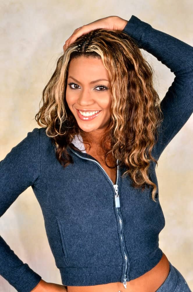 Singer Beyonce Knowles struck a pose with her center-parted curls that are accentuated with blonde highlights during a photoshoot in London on November 18, 2000.