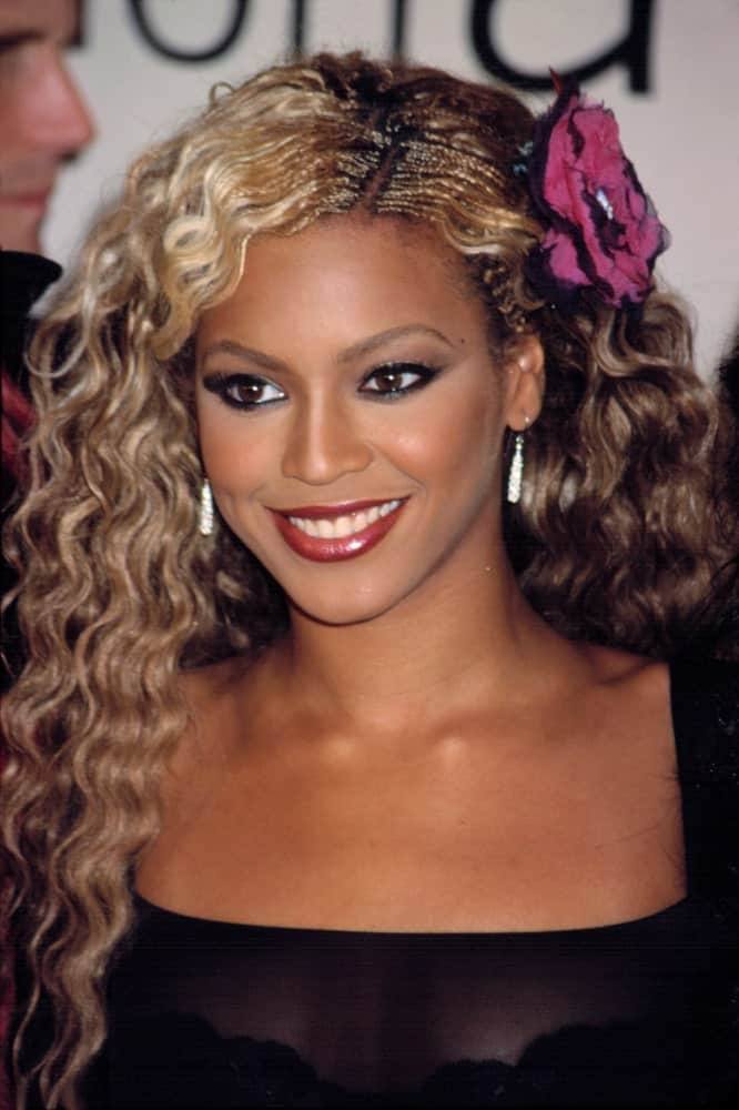 Beyonce exhibited her blonde highlighted curls that are side pinned with a flower during the VH1/ Vogue Fashion Awards in New York on October 19, 2001.