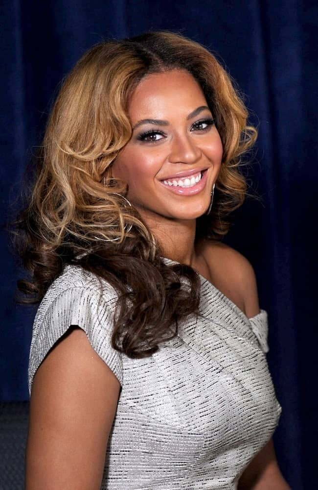 Beyonce Knowles is picture-perfect with her highlighted middle part curls at a public appearance for The Beyonce Cosmetology Center Grand Opening held on March 5, 2010.