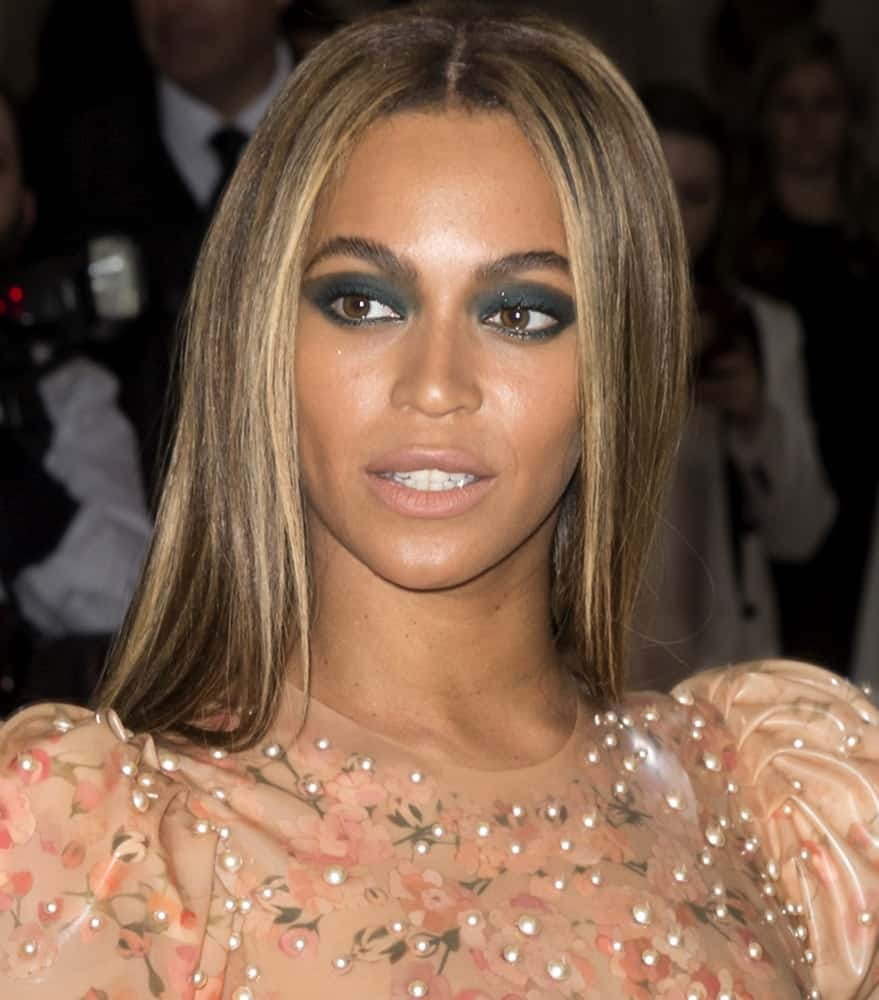 Beyonce Knowles slays in peach latex Givenchy gown and paired her bold make-up with a simple long straight middle parting hairstyle as she attends the Manus x Machina Fashion in an Age of Technology Costume Institute Gala.