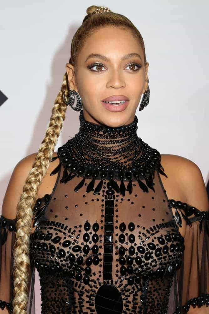 Beyonce Knowles is an epitome of fierce and sultry in her sheer beaded gown and an ultra long slicked back braided ponytail hairstyle as she attends the TIDAL X: 1015 concert at the Barclays Center.
