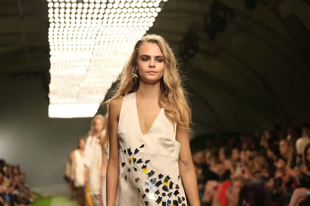 Cara Delevingnewas dressed in a beautiful simple white dress to pair with her long, side-swept wavy sandy blond hairstyle at the London Fashion Week SS14 - Topshop Unique - Catwalk in London on September 15, 2013.
