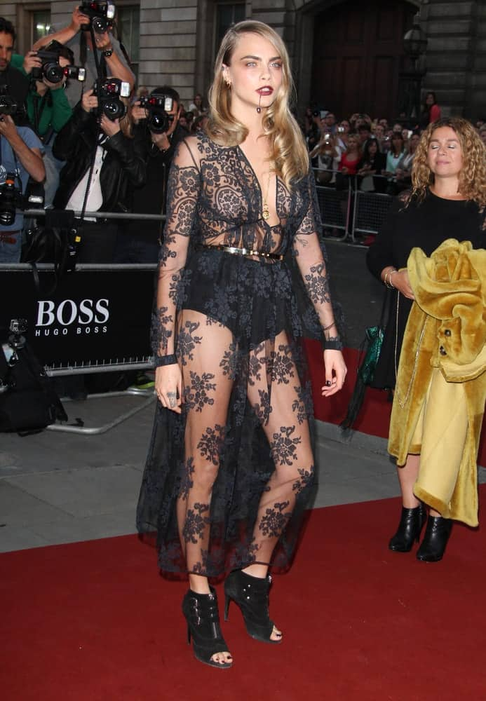 On September 2, 2014, Cara Delevingne attended the GQ Men of the Year awards at The Royal Opera House in London, UK. She was quite stunning in her black sheer dress that she paired with a lip ring and side-swept curly medium-length hairstyle.