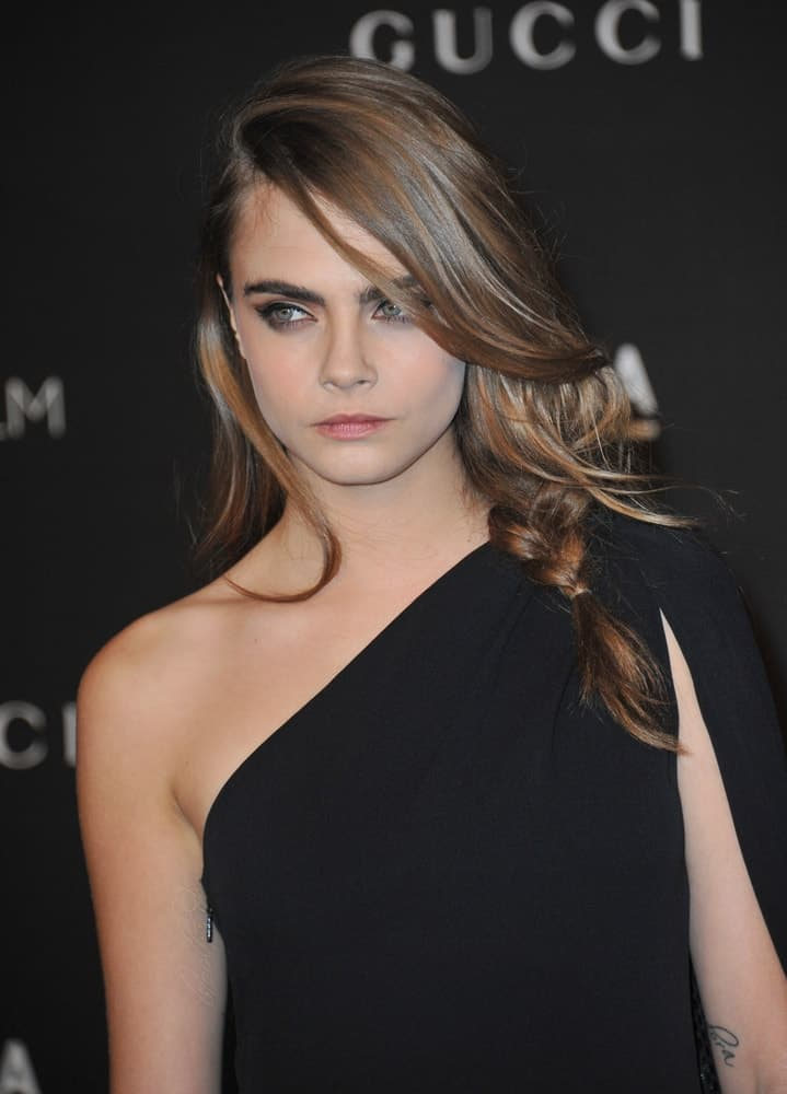 On November 1, 2014, Cara Delevingne wore a charming black dress that she paired with a long highlighted side-swept hairstyle with long side-swept bangs and braids at the 2014 LACMA Art+Film Gala at the Los Angeles County Museum of Art.