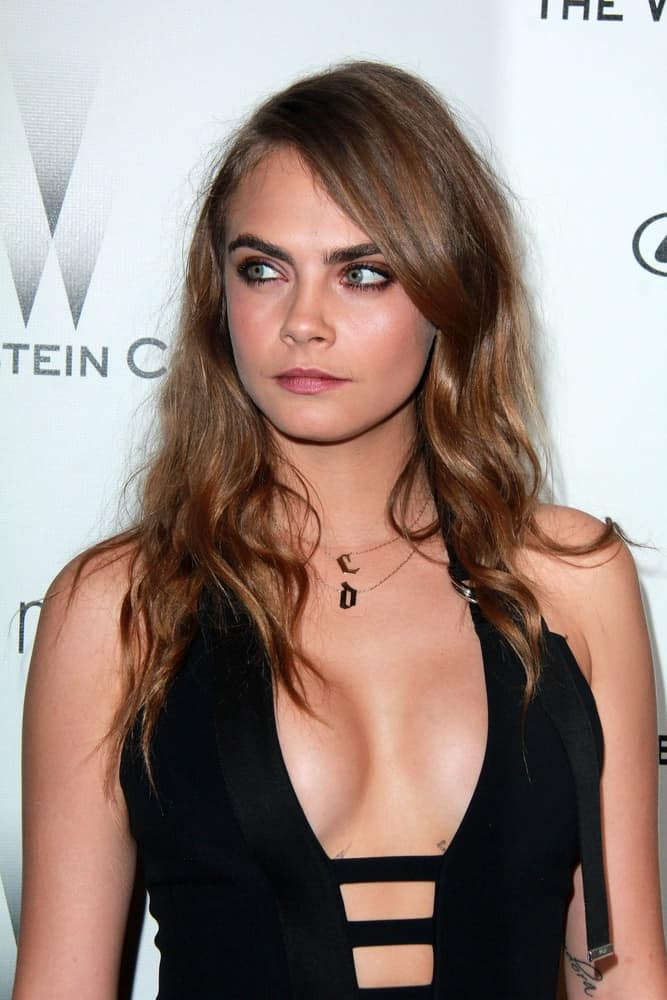 Cara Delevingne's stunning black dress was perfectly paired with her long and highlight wavy brunette hairstyle with long side-swept bangs at the The Weinstein Company / Netflix Golden Globes After Party at a Beverly Hilton Adjacent on January 11, 2015.