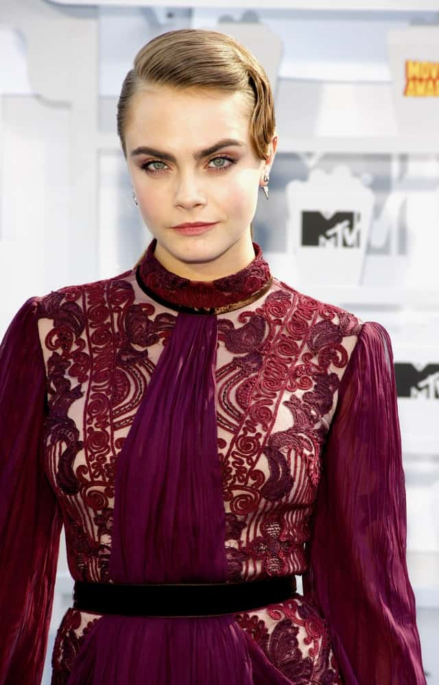 Cara Delevingne went with a slick vintage look to her sandy blond bun hairstyle to go with her red sheer dress at the 2015 MTV Movie Awards held at the Nokia Theatre L.A. Live in Los Angeles, USA on April 12, 2015.