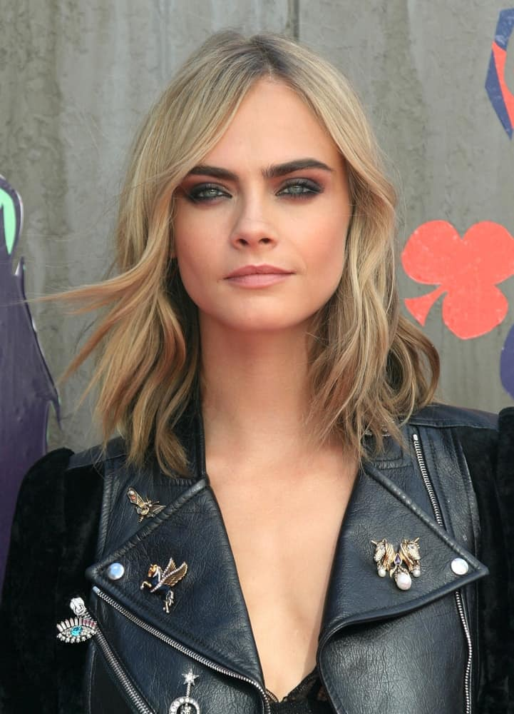 Cara Delevingne was quite cool in her dark gray leather jacket and edgy black outfit to match with her wavy, loose and highlighted sandy blond hairstyle with a slight side-swept finish at the Suicide Squad film premiere on Aug 03, 2016 in London.