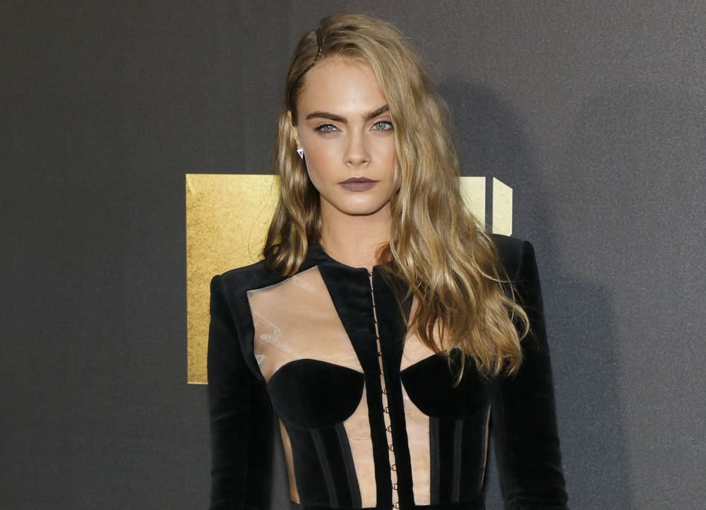 Cara Delevingne wore a fashionable black velvet outfit that complemented her long and wavy highlighted loose hairstyle that has a pinned side-swept finish at the 2016 MTV Movie Awards held at the Warner Bros. Studios in Burbank, USA on April 9, 2016.