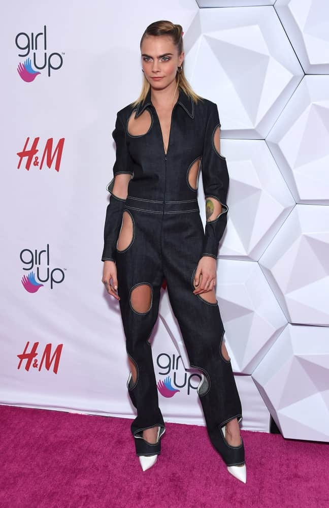 Cara Delevingne wore a fashion-forward denim jumpsuit with her slick highlighted half-up hairstyle when she arrived at the 2nd Annual Girl Up #GirlHero Awards on October 13, 2019 in Beverly Hills, CA.