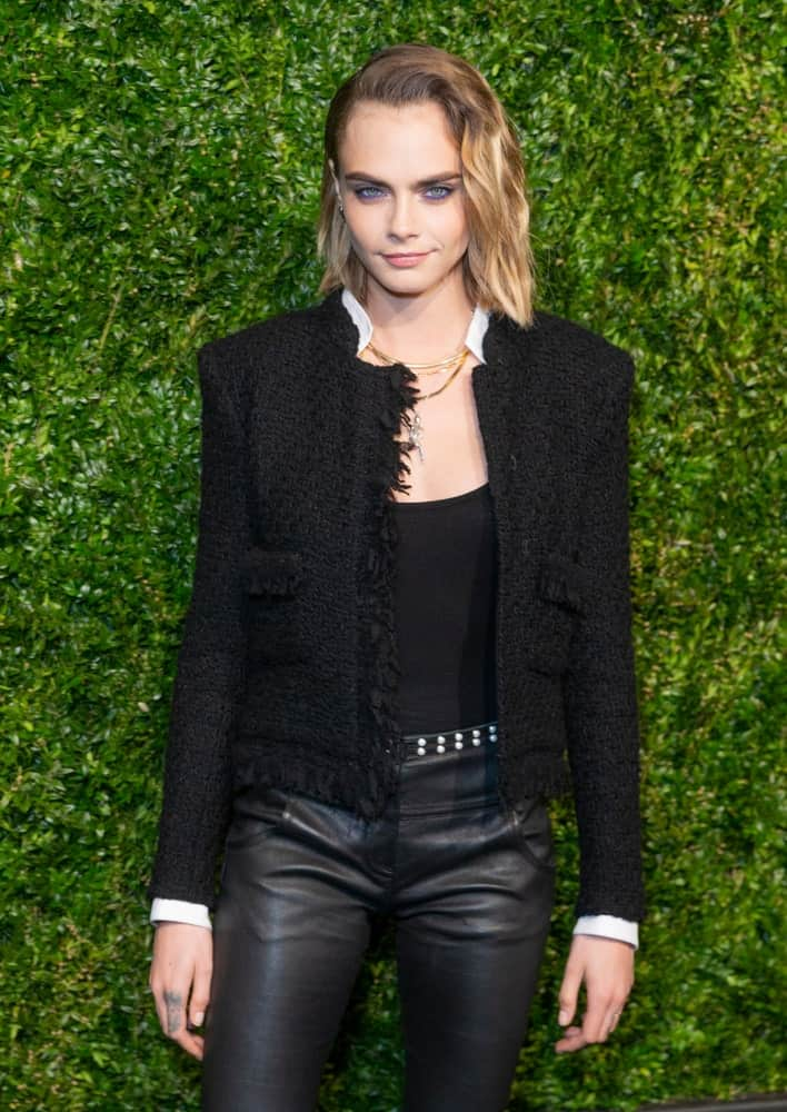 On April 29, 2019, Cara Delevingne wore a Chanel jacket with her pinned side-swept blond hairstyle with highlights and waves when she attended the Chanel 14th Annual Tribeca Film Festival Artists Dinner at Balthazar.