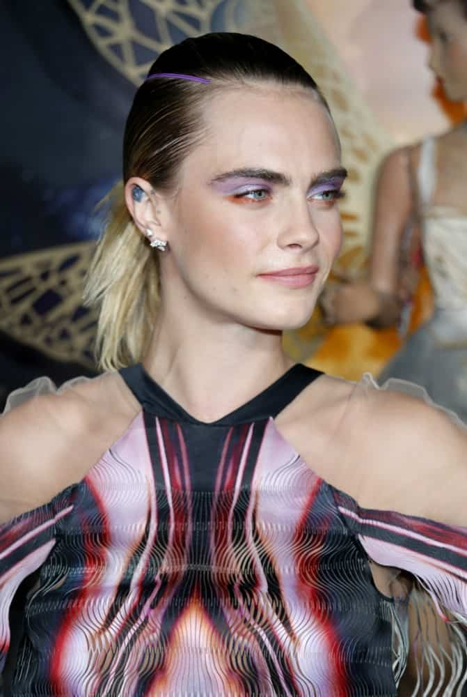 Cara Delevingne wore an elegant colorful dress to pair with her colorful make-up and multi-colored, slick ponytail hairstyle at the Los Angeles premiere of Amazon's 'Carnival Row' held at the TCL Chinese Theatre in Hollywood, USA on August 21, 2019.