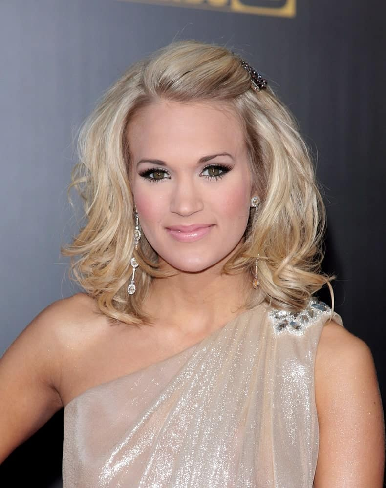 Carrie Underwood looks like a goddess in a nude halter dress along with her medium-length waves that she pinned on one side during the 2009 American Music Awards on November 22, 2009.