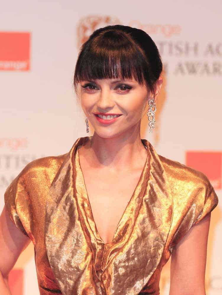 Christina Ricci was in The Winners Room at the 2012 BAFTA's, Royal Opera House Covent Garden, London on February 12, 2012. She wore a golden dress that she paired with her raven bun hairstyle incorporated with blunt bangs.