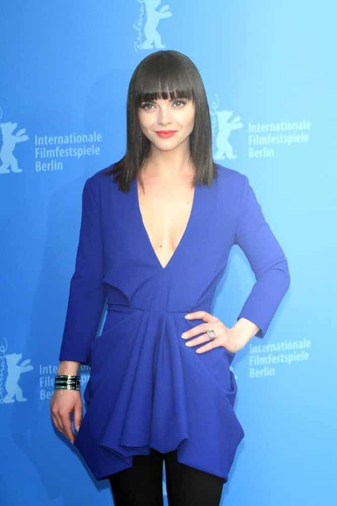 Christina Ricci attended the 'Bel Ami' Photocall during the 62nd Berlinale on February 17, 2012, in Berlin, Germany. She paired her semi-formal blue dress with a straight raven hairstyle that has blunt bangs.