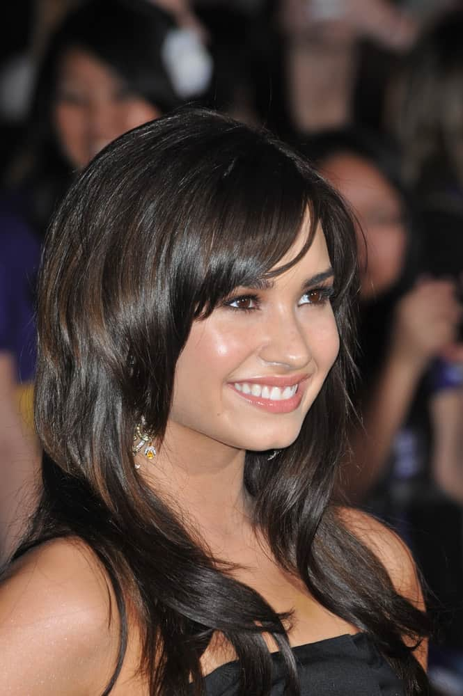 On February 24, 2009, Demi Lovato wore a simple black dress to go with her layered raven hairstyle with bangs and subtle highlights at the world premiere of her new movie