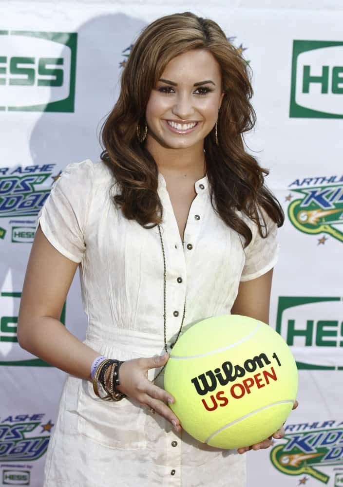 Singer Demi Lovato wore a simple yet lovely white casual dress with her long, highlighted, wavy hairstyle loose on her shoulders at the Arthur Ash stadium for Kids Day at US Open on August 28, 2010 in New York City.