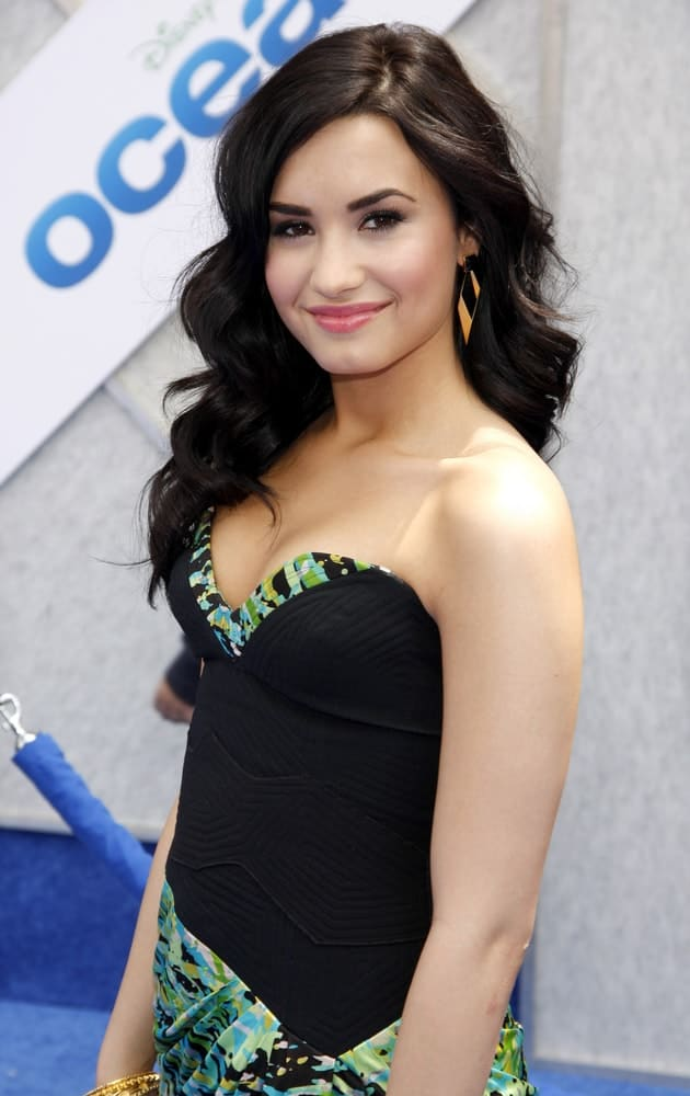 Demi Lovato wore a lovely black strapless dress with her long and wavy raven hairstyle that has a silky side-swept finish at the Los Angeles premiere of 'Oceans' held at the El Capitan Theater in Hollywood, USA on April 17, 2010.