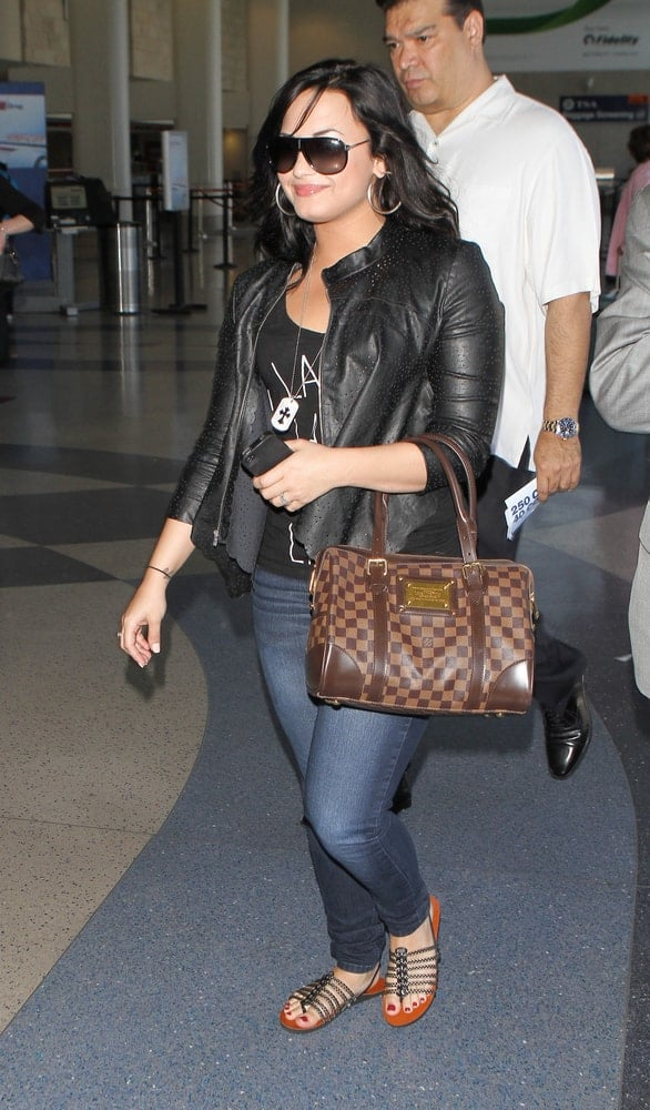 Singer and actress Demi Lovato was seen at LAX Airport on April 23, 2011 in Los Angeles, California. She paired her cool casual outfit with a long and wavy raven hairstyle that has a loose and tousled look.
