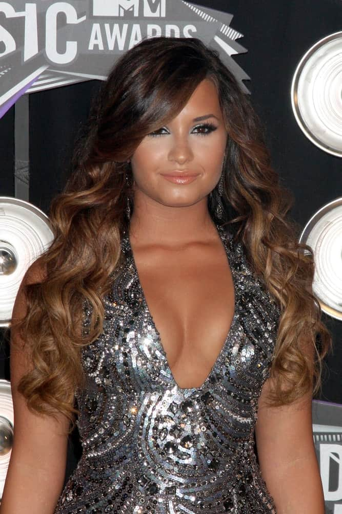 Demi Lovato paired her stunning silver sequined dress with a long and curly highlighted hairstyle that was loose and tousled on her shoulders at the 2011 MTV Video Music Awards at the LA Live on August 28, 2011 in Los Angeles, CA.