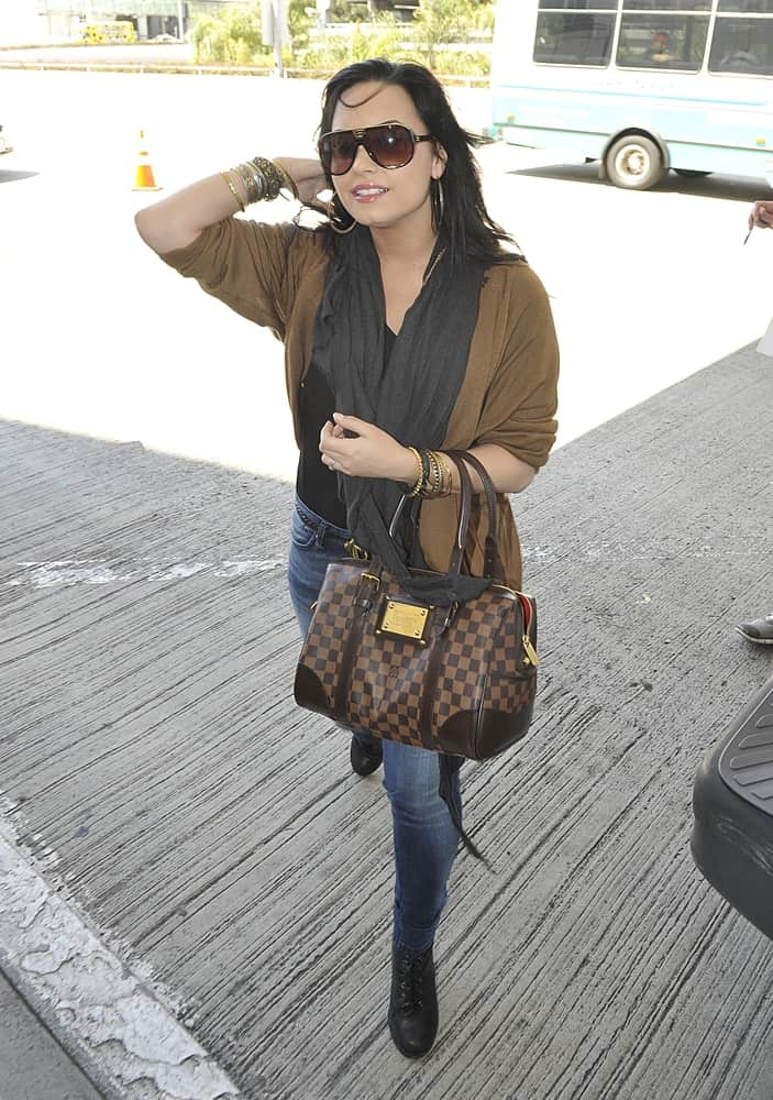 Singer and actress Demi Lovato was seen at the LAX Airport on April 15, 2011 in Los Angeles, California. She wore a simple casual ensemble outfit to go with her long and loose layered raven hairstyle that was tousled in the wind.