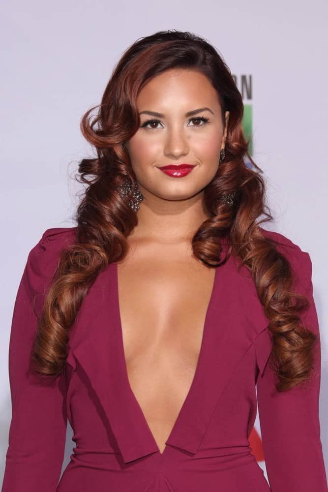 Demi Lovato paired her maroon dress with a unique long and curly highlighted hairstyle with flippy long side-swept bangs at the 12th Annual Latin GRAMMY Awards at Mandalay Bay on November 10, 2011 in Las Vegas, NV.