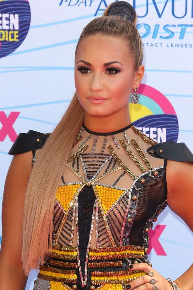 Demi Lovato's colorful sequined dress and confident smile was quite a pair with her long and straight platinum blond hairstyle that was swept up for a slick high ponytail at the 2012 Teen Choice Awards at Gibson Ampitheatre on July 22, 2012 in Los Angeles, CA.