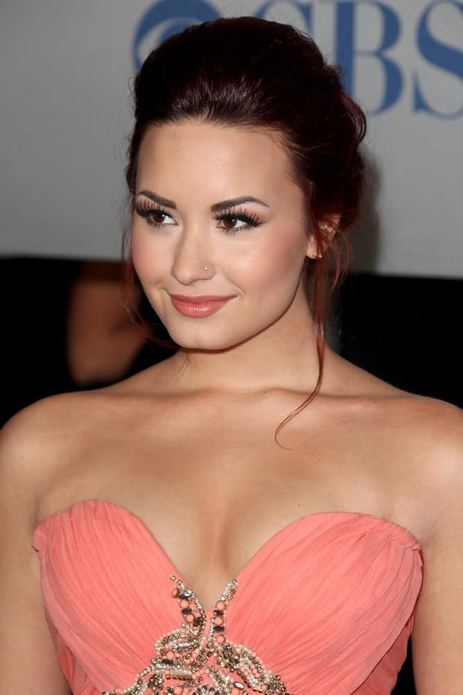 Demi Lovato wore a gorgeous peach strapless dress to match with her loose upstyle that has a dark red tint to its loose tendrils when she arrived at the People's Choice Awards 2012 at Nokia Theater at LA Live on January 11, 2012 in Los Angeles, CA.