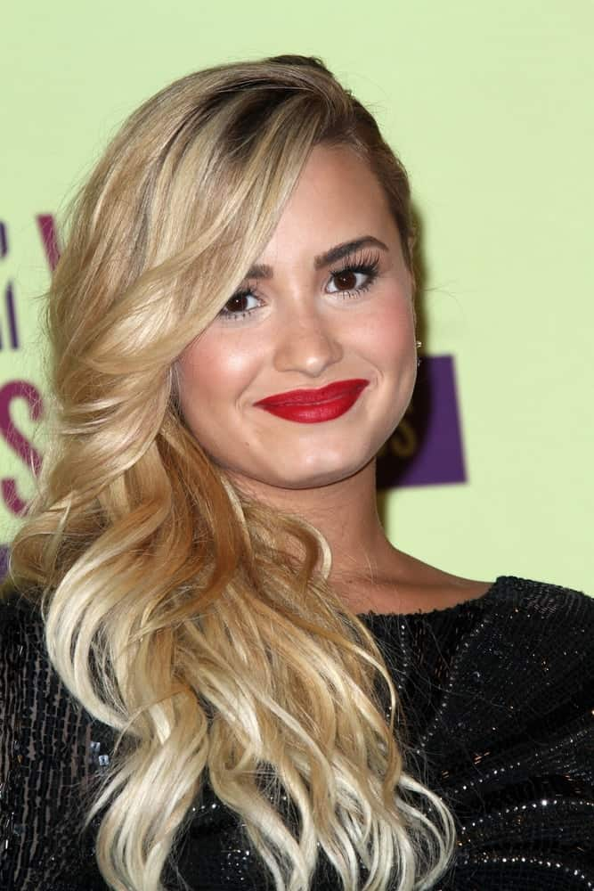 Demi Lovato's black sequined dress complemented her bright blond curls side-swept to her shoulder with a slight tousle and side-swept bangs at the 2012 Video Music Awards Press Room, Staples Center in Los Angeles, CA on September 6, 2012.