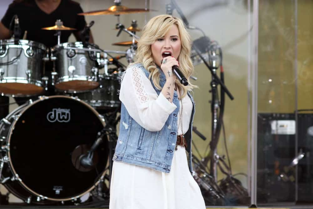 Demi Lovato performed at the 'Good Morning America' concert series in Central Park on June 28, 2013 in New York City. She wore a long white dress with her denim jacket and shoulder-length curly blond hairstyle with long side-swept bangs.