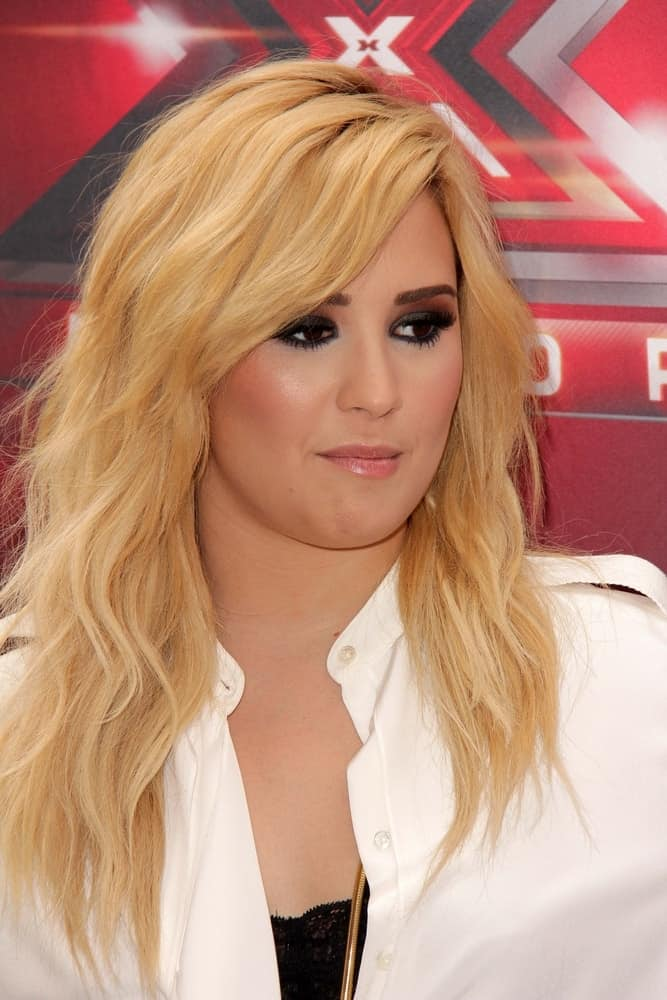 Demi Lovato wore a bright white dress with her bright blond hairstyle that has layers, waves and a slight tousle at the