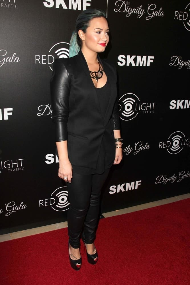 Demi Lovato's red lips paired quite well with her black leather outfit and tight ponytail with blue highlights at the Dignity Gala and Launch of Redlight Traffic App at Beverly Hilton Hotel on October 18, 2013 in Beverly Hills, CA.