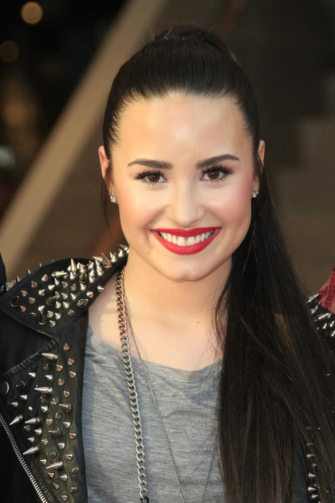Demi Lovato was at the Topshop Topman LA Grand Opening at The Grove on February 14, 2013 in Los Angeles, California. She paired her casual gray shirt with a cool black leather jacket and a slick and straight raven high ponytail hairstyle.