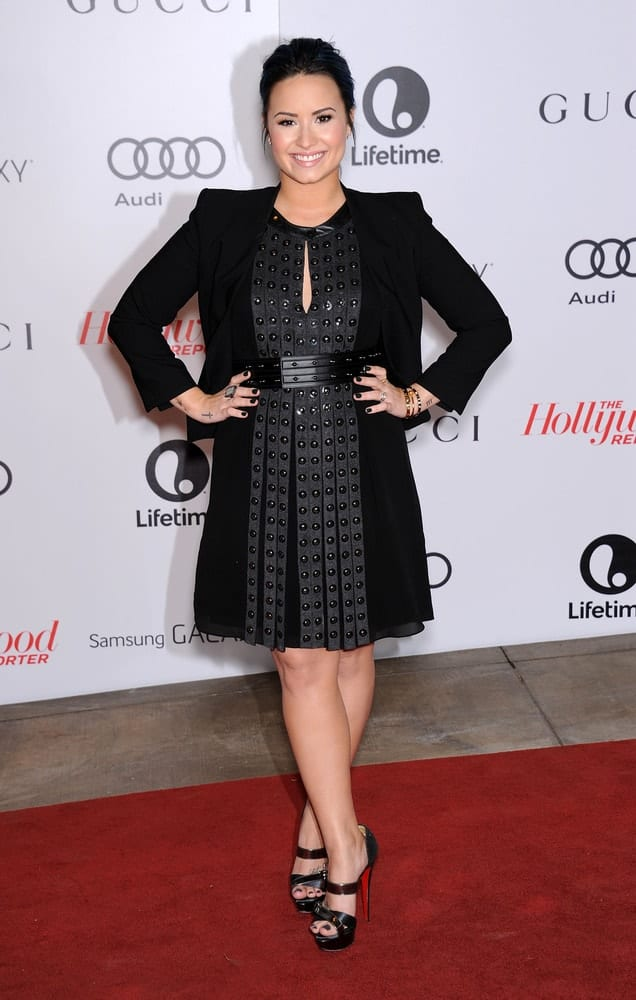 Demi Lovato was in attendance at the Women in Entertainment Breakfast 2013 on December 11, 2013 in Hollywood, CA. She paired her beautiful black heels with a dress and jacket topped with a simple dark bun hairstyle with loose tendrils on the side.
