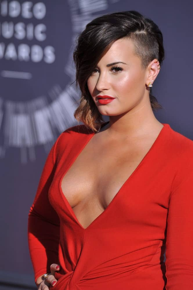 On August 24, 2014, Demi Lovato was quite lovely with her red dress, red lips and red nails to pair with her highlighted side-swept chin-length hairstyle with a shaved side of the head at the 2014 MTV Video Music Awards at the Forum in Los Angeles.