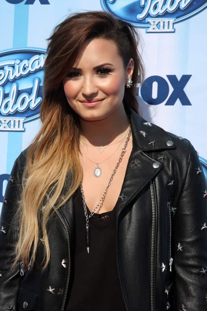Demi Lovato wore a cool black leather jacket to complement her long side-swept highlighted tousled hairstyle with a shaved side and long side-swept bangs at the American Idol Season 13 Finale at Nokia Theater at LA Live on May 21, 2014 in Los Angeles, CA.