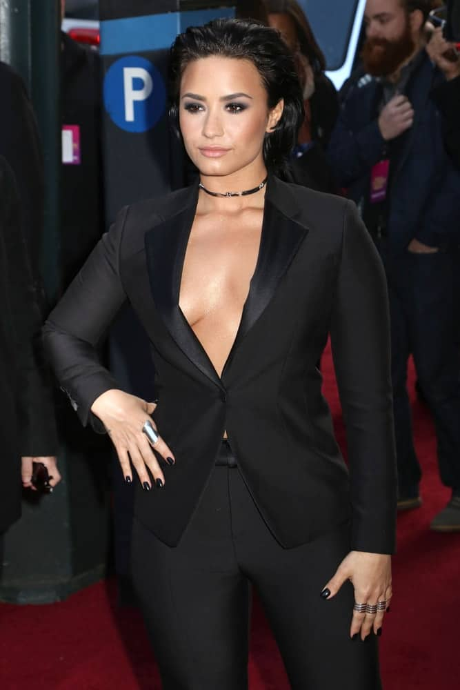 Demi Lovato attended the Billboard's 10th Annual Women in Music event at Cipriani on December 11, 2015 in New York City. She wore an all-black suit outfit with her tousled brushed back raven hairstyle with layers.