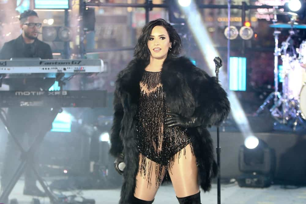 Recording artist Demi Lovato performed on stage during Dick Clark's New Year's Rockin' Eve at Times Square on December 31, 2015 in New York City. She looked amazing in her fur outfit and tousled side-swept raven chin-length hairstyle.