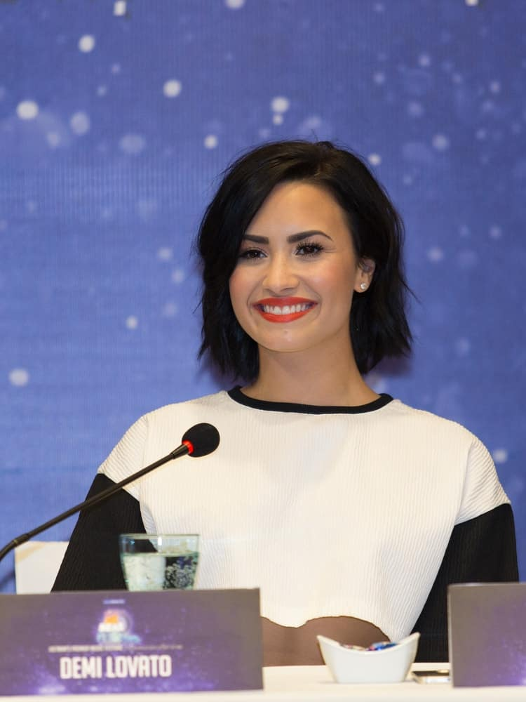 On May 8, 2015, Demi Lovato was at the press conference for the event YAN Beatfest 2015 in Vietnam. She wore a simple black and white casual outfit that went quite well with her short tousled bob hairstyle with layers and side-swept bangs.