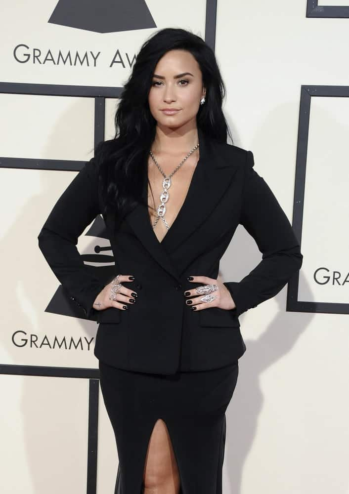 Demi Lovato wore a black smart formal outfit with her long and tousled side-swept raven hairstyle with waves  and layers at the 58th GRAMMY Awards held at the Staples Center in Los Angeles, USA on February 15, 2016.
