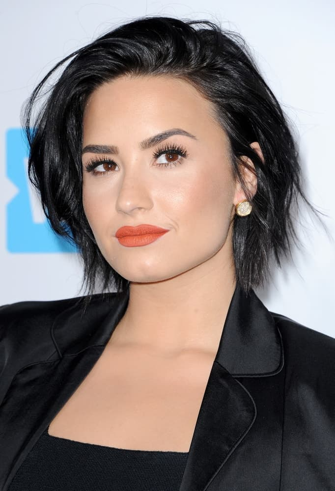 Demi Lovato's short raven hair was tossed up for a tousled side-swept finish to match with her black outfit at the WE Day California held at the Forum in Inglewood, USA on April 7, 2016.