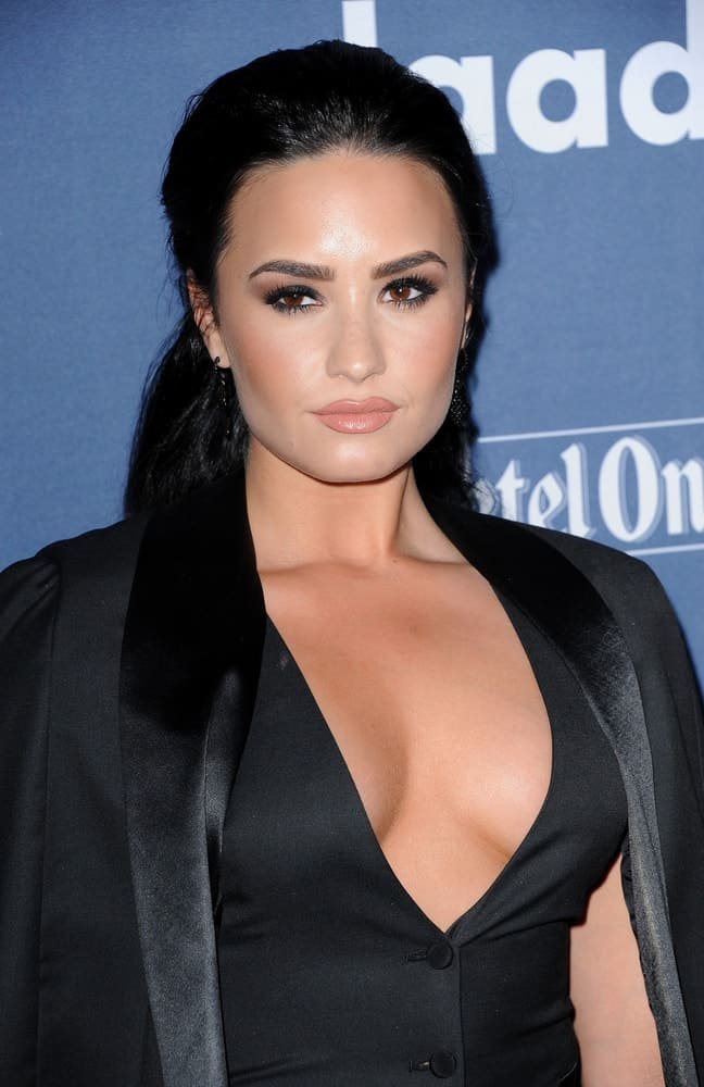 Demi Lovato wore an all-black smart outfit with her half-up hairstyle that has a slick raven finish at the 27th Annual GLAAD Media Awards held at the Beverly Hilton Hotel in Beverly Hills, USA on April 2, 2016.