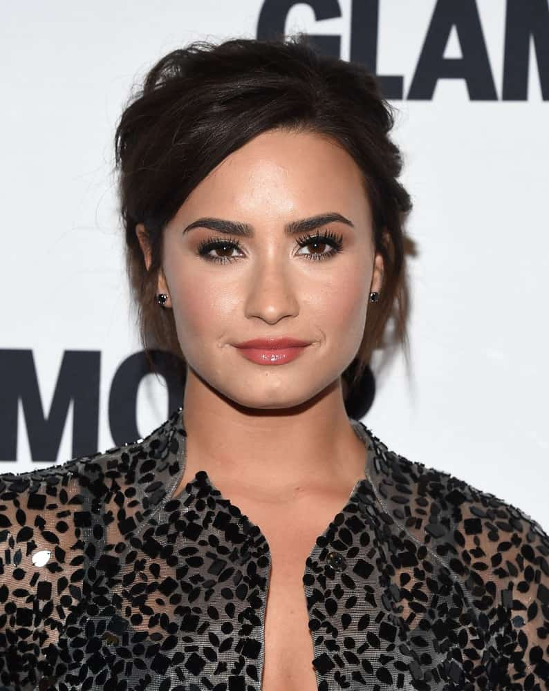 Demi Lovato was quite lovely with her shiny red lips and messy raven upstyle bun hairstyle with side-swept bangs when she arrived at the Glamour Celebrates Women of the Year Awards 2016 on November 14, 2016 in Hollywood, CA.